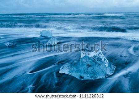 Stock Photo crashing waves around ice rocks on the black sanded diamond beach, iceland april 2018