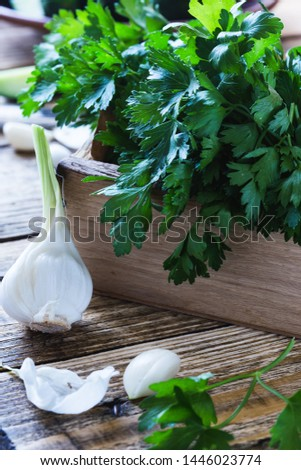 Crate of freshly picked organic  parsley, roasted cherry  tomatoes, and fresh garlic on rustic wooden table, plant based food, close up, selective focus