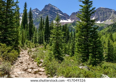 Crater Lake Trail - A rugged hiking trail winding through a pine forest at base of Maroon Bells, Aspen, Colorado, USA.