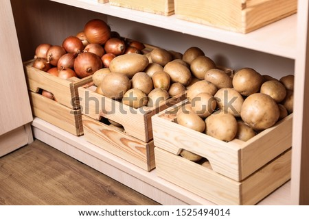 Crates with potatoes and onions on shelf. Orderly storage
