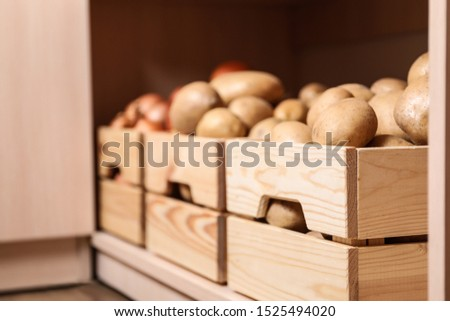 Crates with potatoes on shelf, closeup. Orderly storage