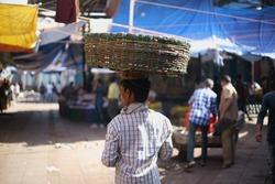 Crawford Market, Dhobi Talao, Chhatrapati Shivaji Terminus Area, Fort, Mumbai, Maharashtra, India - October 25, 2017 - A hard working man/ laborer is seen carrying a fruit basket on his head