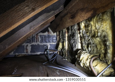 Photo of  Crawl space under the eves of a house showing old fibreglass insulation, pipework, rafters, breezeblock construction and old boarding.