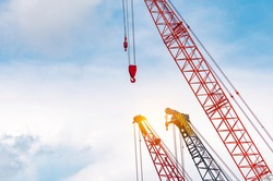 Crawler crane against blue sky and white clouds. Real estate industry. Red crawler crane use reel lift up equipment in construction site. Crane for rent. Crane dealership for construction business.
