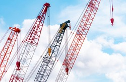 Crawler crane against blue sky and white clouds. Red crawler crane use reel lift up equipment in construction site. Crane for rent. Crane dealership for construction business concept.