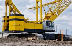 Crawler crane on a construction site with focus on the machine deck, counterweight and treads.