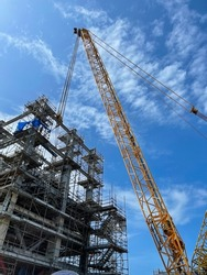 Crawler cranes are lifting steel beams to install, for building construction steel structures.