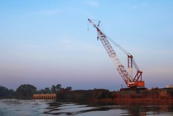 Crawler cranes used for rebuilding bridges  near the river in Thailand