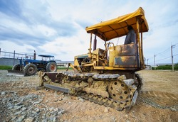 Crawler Dozer Yellow parked in a clearing in preparation for topsoil and beautiful blue sky in the background. The concept of a bulldozer prepares the topsoil for construction.