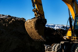 Crawler excavator. The excavator in the process of work digs out the earth and pours it onto the site. Works on a clear winter day against the blue sky.