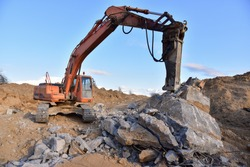 Crawler excavator with hydraulic breaker hammer for the destruction of concrete and hard rock at the construction site or quarry.  Jackhammer using without blasting method. Hard rock demolition