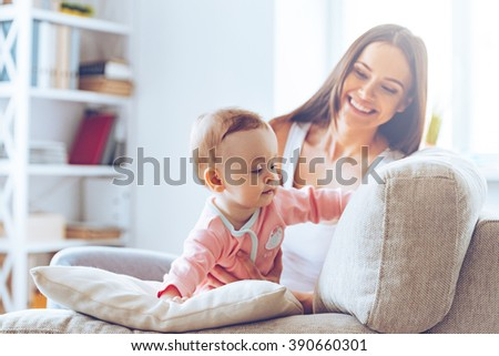 Crawling on sofa. Little baby girl crawling on sofa and leaning on cushion while her mother sitting at background