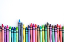 Crayons and pastels lined up isolated on white background with copy space