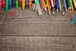 Crayons and pencils on wooden background