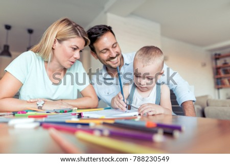 Crayons drawing family,father and mather looks how son draws.Teacher and pedagogy, art therapy.Small artist with crayon. #788230549