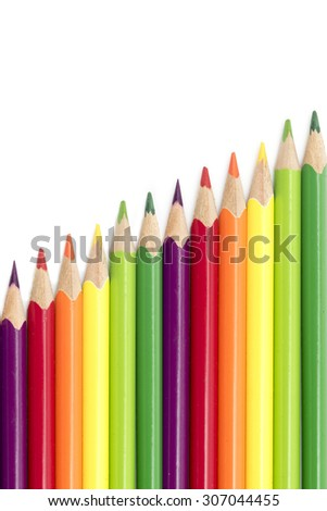 crayons or colored pencils in a diagonal row isolated on a white background with copy space, vertical