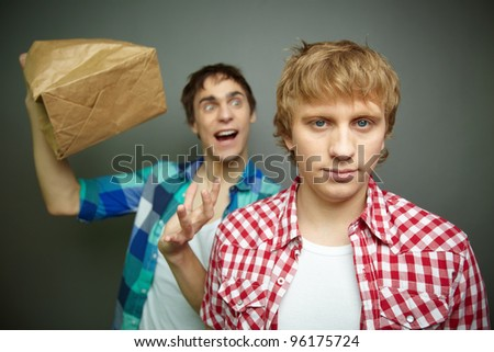 Crazily looking guy exploding paper bag behind his friend's back, fool's day series or birthday party
