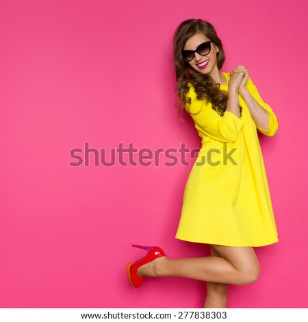 Crazy About New Shoes. Excited girl in yellow mini dress posing on one leg against pink background. Three quarter length studio shot.