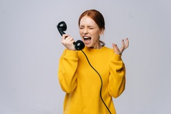 Crazy angry young woman in stylish yellow sweater talking on retro phone and screaming in handset against isolated white background. Pretty redhead lady model emotionally showing facial expressions.