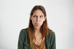 Crazy attractive woman showing her tongue frowning eyes looking aside having joy. Caucasian female standing against white wall blowing her cheeks showing tongue being angry showing her discontent