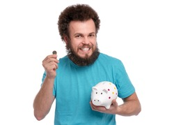 Crazy bearded Man with funny Curly Hair holding Piggy Bank and coin, isolated on white background. Saving Money concept. Male putting coin in his piggybank.