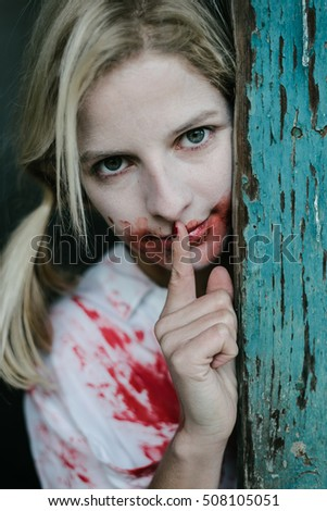 Stock Photo Crazy blonde woman covered with blood making silence gesture. Halloween concept.