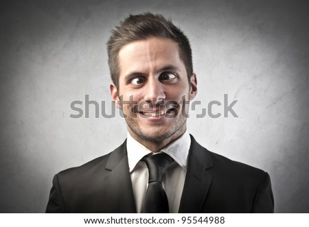 Crazy businessman making funny faces - stock photo