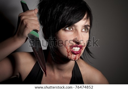 Crazy cannibal woman with blood on her face and knife in hands