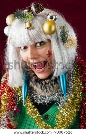 Crazy Christmas woman. Studio shot against a red background.