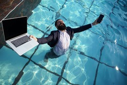 Crazy comic business. Excited business man in suit with laptop and mobile phone on swimming pool. Funny businessman relaxing with laptop