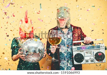 Crazy couple celebrating new year eve wearing chicken and dinosaur t-rex mask - Young trendy people having fun drinking champagne and listening music with vintage boombox - Absurd and holidays concept