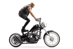 Crazy daredevil biker riding a chopper and standing on the seat isolated on white background
