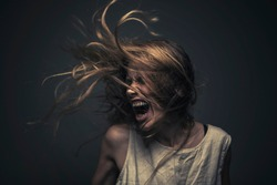Crazy, deranged young woman screaming with frustration, expressing madness and rage
