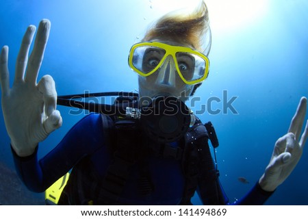 Crazy diver showing ok signal with bulging eyes