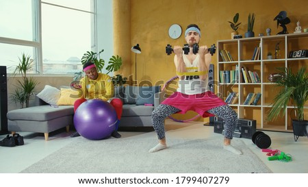Crazy fitness fan energetic man lifting up dumbbells and stretching legs simultaneosly. Lazy afro-american obese man resting down supporting his friend. Fun concept. Foto stock ©