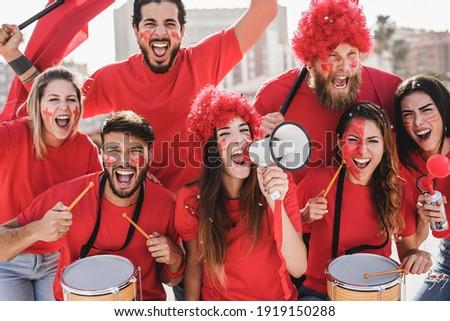 Crazy football fans having fun outside stadium for soccer match - Focus on center girl face