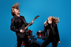 Crazy funky two people youth team rock band enjoy punk festival tour man play bass guitar woman sing song, composition mic hair air fly blow wind isolated over bright shine color background