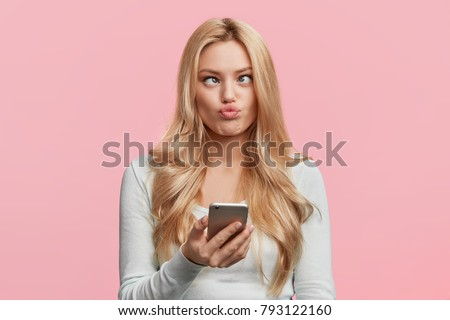 Crazy funny comic female crosses eyes, pouts lips, makes grimace, foolishes, holds cell phone, involved in games online, isolated over pink background. Facial expressions. Childish woman plays fool