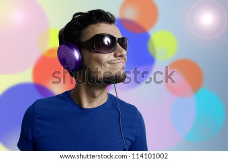 Crazy guy with headphones on colorful background - stock photo
