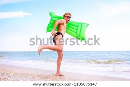 Crazy happy man with swimming mattress runs in the sea #1105895147