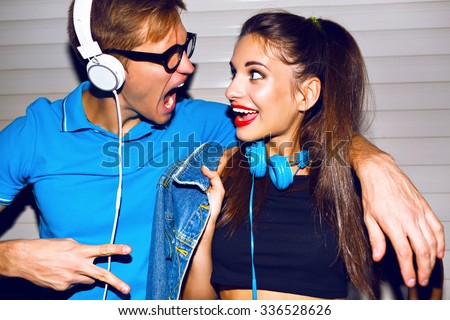 Crazy hipster couple having fun, screaming singing and smiling, looking to each other , having fun at romantic date, listening music at big headphones, trendy bright clothes.