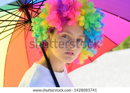 Crazy hipster girl. fashion girl with colorful hair wig and umbrella. kid in summer camp. happy youth party. autumn weather. optimist. positive cheerful. spring vibes. protection. rainbow umbrella.