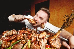 Crazy hungry man eating mix grill meat. Emotional content for restaurant promo. Cheat day. Meat lover. Lamb chops, chicken tikka, kebab, lamb, beef steak.