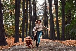 Crazy jogging with a dog in the autumn park. A young beautiful woman runs with a purebred dog that pulls on a leash and laughs.