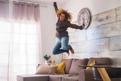 crazy middle age woman jump at home over the sofa to celebrate success - joyful and happiness people concept - craziness and freedom lifestyle for independent modern female - house joyful people