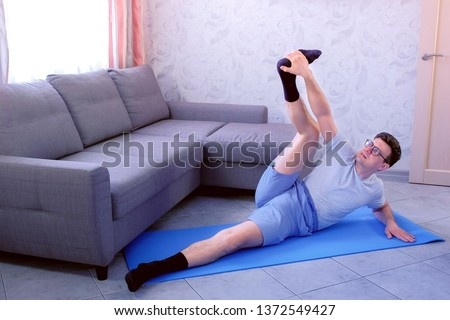 Crazy nerd man in glasses is trying to stretch his legs laying on the mat at home. Sport humor concept.