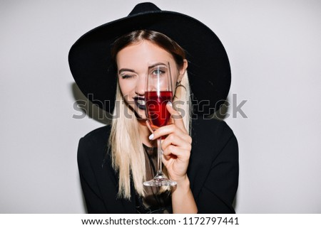 Crazy party time of beautiful woman in elegant black hat with a glass of champagne celebrating new year, birthday, halloween, having fun, dancing,drinking alcohol cocktails.Emotion face, smile #1172797441