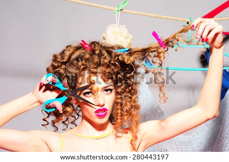 Crazy playful young beautiful fashionable woman with curly hair holding scissors cutting curle looking forward indoor on grey wall background copyspace, horizontal picture