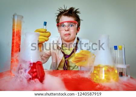 Crazy scientist. Young boy performing experiments #1240587919