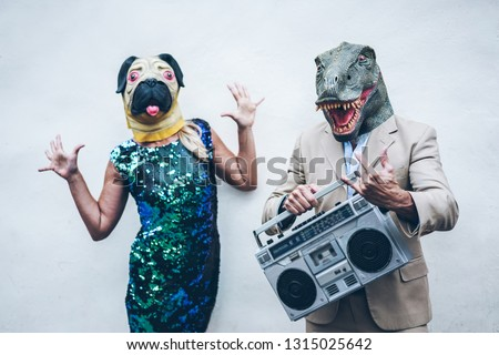 Crazy senior couple dancing for party wearing t-rex and chicken mask - Old trendy people having fun listening music with boombox stereo - Absurd and funny trend concept - Focus on dino face